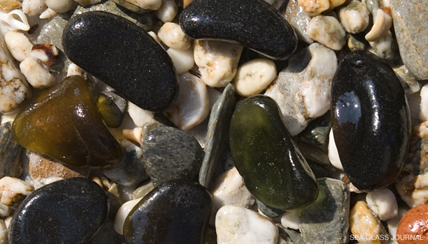 Black sea glass can look like stones on the beach.